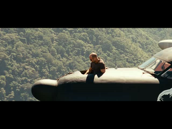 Jason Statham riding in the nose of the aircraft.