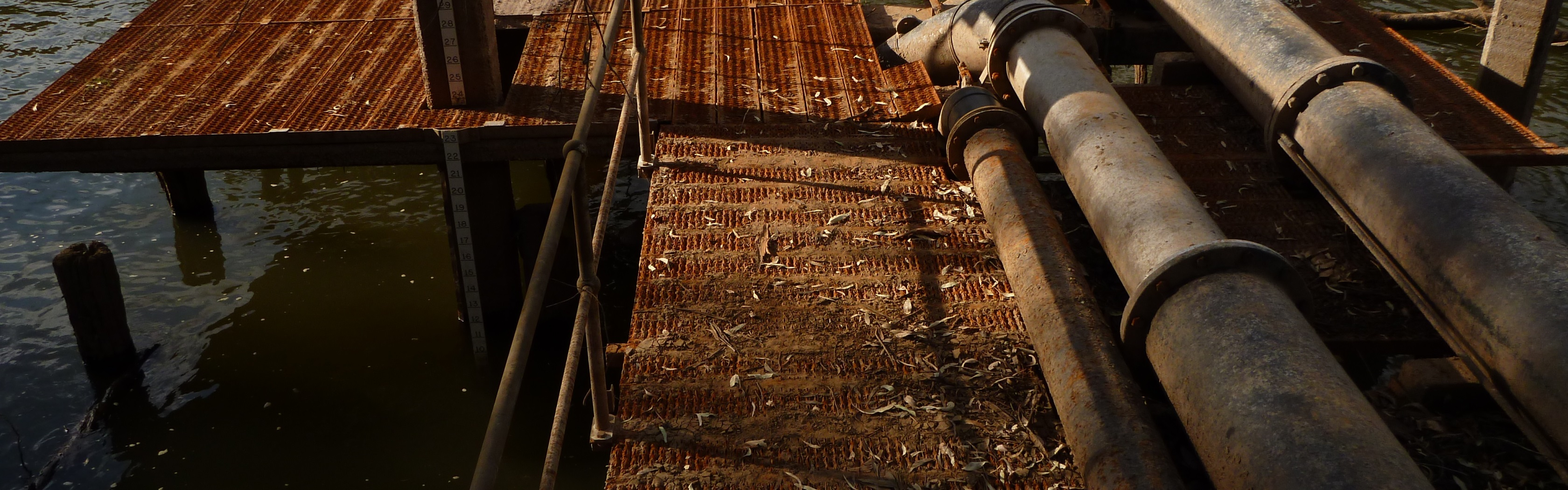 Dual screen Linux wallpaper. Rusty platform and water pipes.